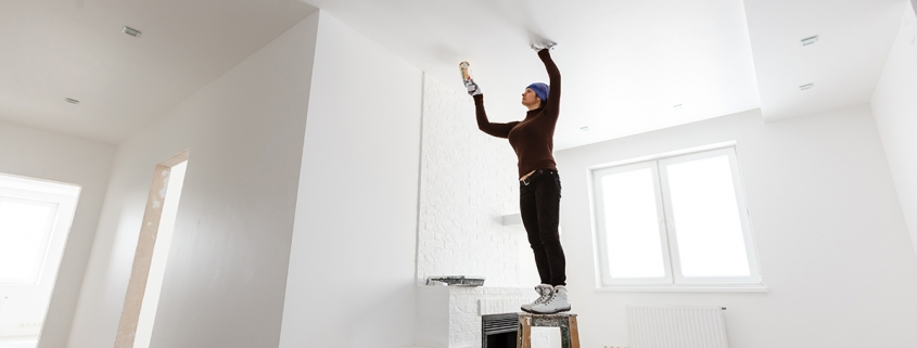 Woman paints ceiling with brush at home